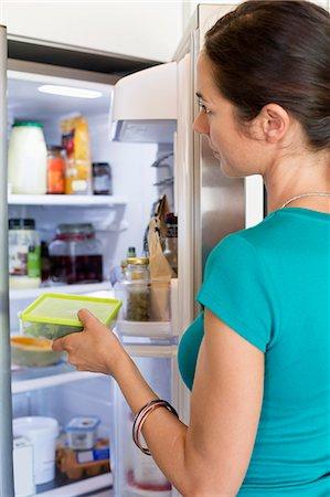 fridge - Woman putting food in a refrigerator Stock Photo - Premium Royalty-Free, Code: 6108-06905998