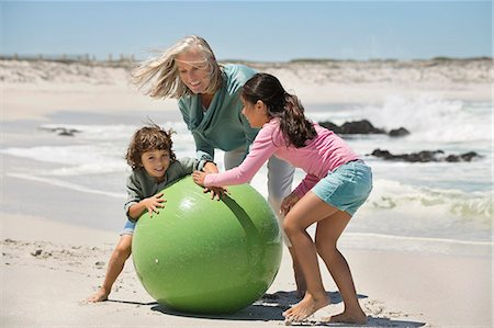 Woman playing with her grandchildren on the beach Stock Photo - Premium Royalty-Free, Code: 6108-06905903