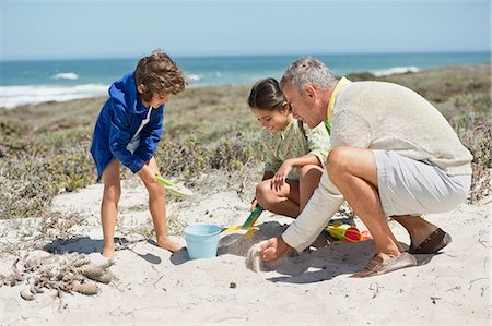 Children playing in sand with their grandfather on the beach Stock Photo - Premium Royalty-Free, Code: 6108-06905917
