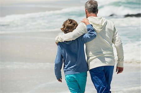 Man walking with his grandson on the beach Stock Photo - Premium Royalty-Free, Code: 6108-06905921