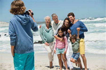 Boy filming his family with a home video camera on the beach Stock Photo - Premium Royalty-Free, Code: 6108-06905926