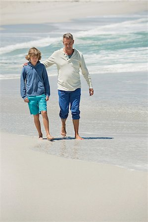 Man walking with his grandson on the beach Stock Photo - Premium Royalty-Free, Code: 6108-06905937