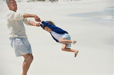 Man playing with his grandson on the beach Stock Photo - Premium Royalty-Free, Code: 6108-06905934
