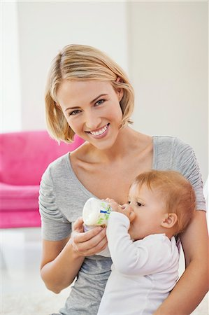 Woman feeding milk her baby with a bottle Stock Photo - Premium Royalty-Free, Code: 6108-06906041