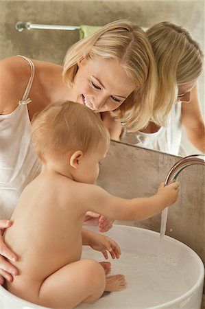 Woman giving bath to her baby in a wash bowl Stock Photo - Premium Royalty-Free, Code: 6108-06906042