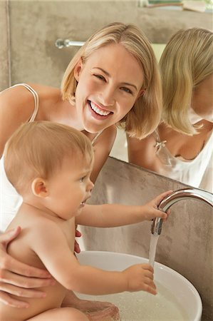 Woman giving bath to her baby in a wash bowl Stock Photo - Premium Royalty-Free, Code: 6108-06906084