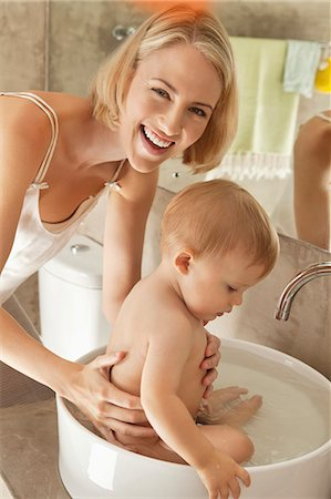 Woman giving bath to her baby in a wash bowl Stock Photo - Premium Royalty-Free, Code: 6108-06906090