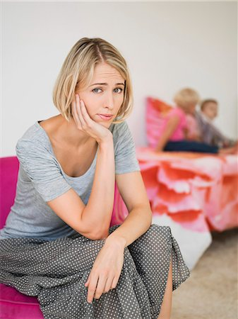Portrait of a woman looking worried with her children in the background Stock Photo - Premium Royalty-Free, Code: 6108-06906096