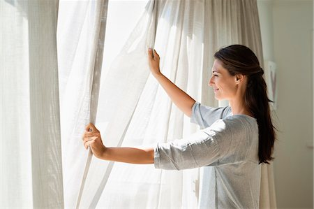 Woman opening the curtain of a window Stock Photo - Premium Royalty-Free, Code: 6108-06906010