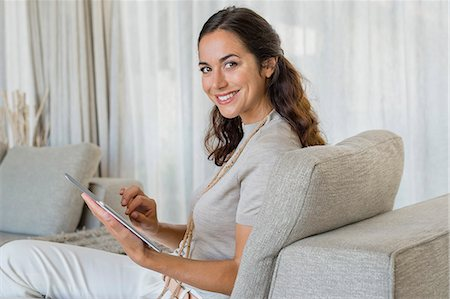 Beautiful woman using a digital tablet and smiling on a couch Stock Photo - Premium Royalty-Free, Code: 6108-06906014