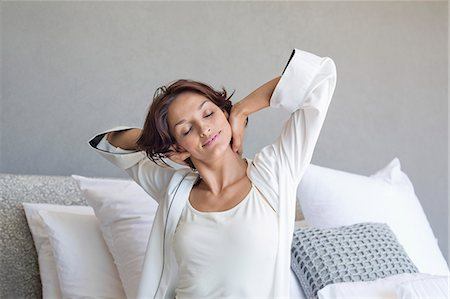 stretch - Woman stretching on the bed Stock Photo - Premium Royalty-Free, Code: 6108-06906015