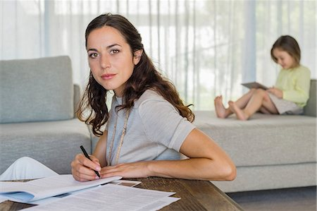 sit - Woman doing paperwork with her daughter using a digital tablet in the background Stock Photo - Premium Royalty-Free, Code: 6108-06906023