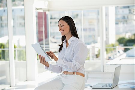 property release - Businesswoman holding a digital tablet and smiling in an office Stock Photo - Premium Royalty-Free, Code: 6108-06906166