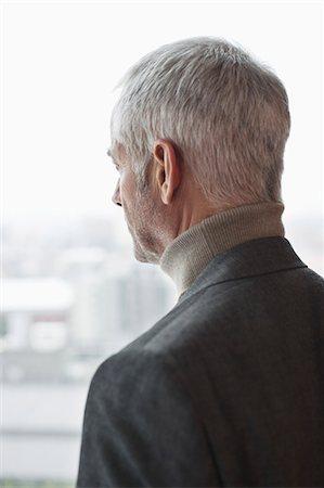 Man looking through a window Stock Photo - Premium Royalty-Free, Code: 6108-06906188