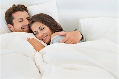 Smiling couple lying on the bed Stock Photo - Premium Royalty-Free, Code: 6108-06906198