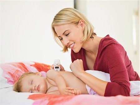 Smiling Woman looking at her sleeping baby Stock Photo - Premium Royalty-Free, Code: 6108-06906102