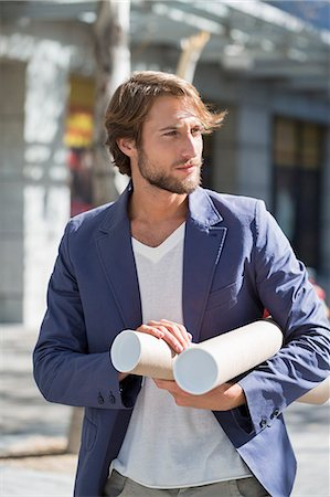 Architect carrying paper rolls Stock Photo - Premium Royalty-Free, Code: 6108-06906139