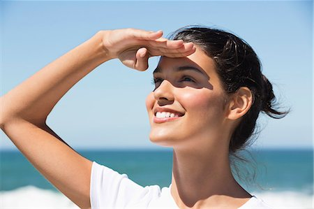 Beautiful woman shielding eyes on the beach Stock Photo - Premium Royalty-Free, Code: 6108-06906259