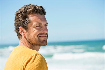 summer - Man smiling on the beach Stock Photo - Premium Royalty-Free, Code: 6108-06906272