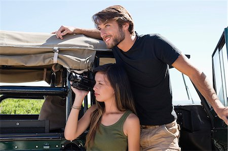 Woman filming with a video camera with her boyfriend on SUV Stock Photo - Premium Royalty-Free, Code: 6108-06906279