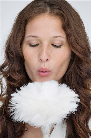 feather  close-up - Woman blowing on a feather duster Stock Photo - Premium Royalty-Free, Code: 6108-06906354