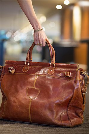 Close-up of a woman's hand picking up a leather purse Stock Photo - Premium Royalty-Free, Code: 6108-06906300
