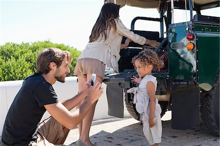 Man taking a picture of his daughter with a smartphone beside a SUV Stock Photo - Premium Royalty-Free, Code: 6108-06906317