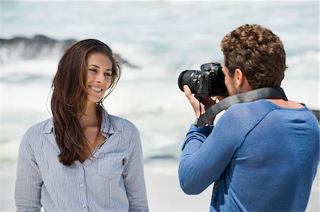 Man taking a picture of his wife with a camera on the beach Stock Photo - Premium Royalty-Free, Code: 6108-06906316