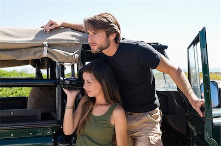 Woman filming with a video camera with her boyfriend on SUV Stock Photo - Premium Royalty-Free, Code: 6108-06906330