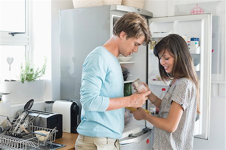 fridge - Couple looking at food product in front of a refrigerator in the kitchen Stock Photo - Premium Royalty-Free, Code: 6108-06906415