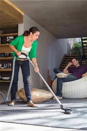 Woman cleaning house with a vacuum cleaner with her husband sitting on a seat Stock Photo - Premium Royalty-Free, Code: 6108-06906416