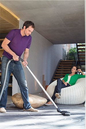 Man cleaning house with a vacuum cleaner with his wife sitting on a seat Stock Photo - Premium Royalty-Free, Code: 6108-06906430