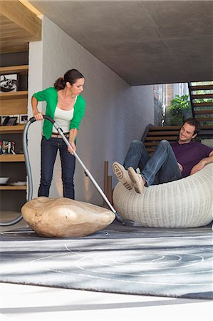 Woman cleaning house with a vacuum cleaner with her husband sitting on a seat Stock Photo - Premium Royalty-Free, Code: 6108-06906432