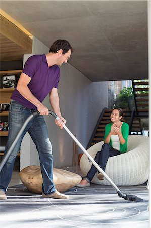 Man cleaning house with a vacuum cleaner with his wife sitting on a seat Stock Photo - Premium Royalty-Free, Code: 6108-06906434