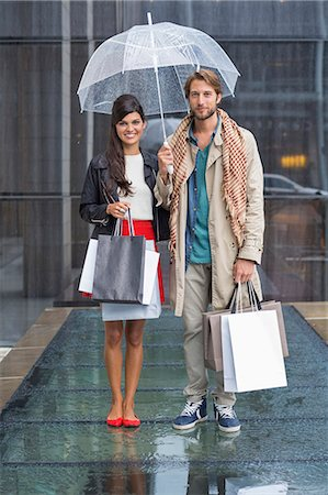 people with umbrellas in the rain - Couple standing with shopping bags during rain Stock Photo - Premium Royalty-Free, Code: 6108-06906566