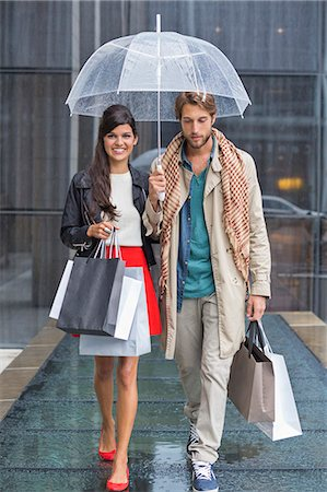 people with umbrellas in the rain - Couple with shopping bags sheltering under umbrella in rain Stock Photo - Premium Royalty-Free, Code: 6108-06906574