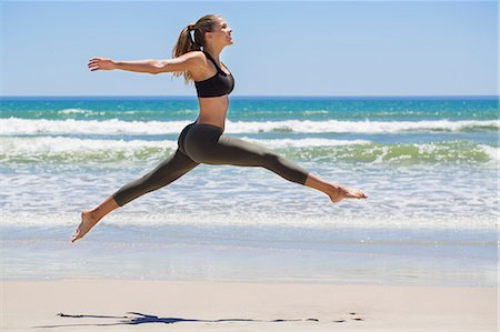 Woman jumping on the beach Stock Photo - Premium Royalty-Free, Code: 6108-06906594