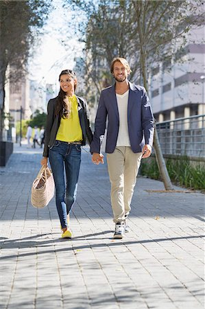 Happy couple walking on a street Stock Photo - Premium Royalty-Free, Code: 6108-06906504