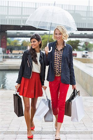 people with umbrellas in the rain - Female friends walking with shopping bags and smiling Stock Photo - Premium Royalty-Free, Code: 6108-06906520