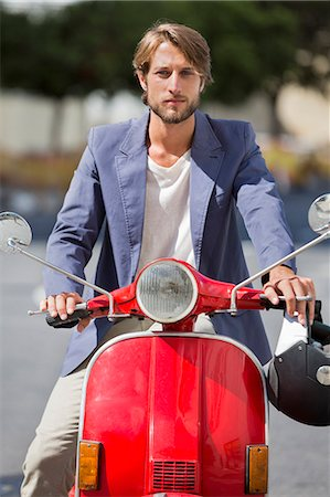 Man riding a scooter Stock Photo - Premium Royalty-Free, Code: 6108-06906535