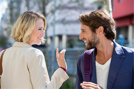flirting - Man and woman smiling at each other Stock Photo - Premium Royalty-Free, Code: 6108-06906538
