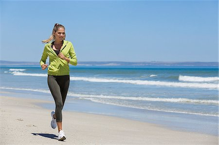 Woman jogging on the beach Stock Photo - Premium Royalty-Free, Code: 6108-06906609