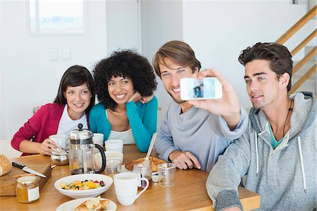 Friends taking picture of themselves with a mobile phone Stock Photo - Premium Royalty-Free, Code: 6108-06906772