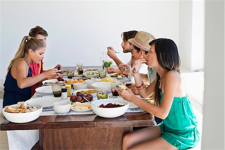 Friends eating lunch at dining table Stock Photo - Premium Royalty-Free, Code: 6108-06906790