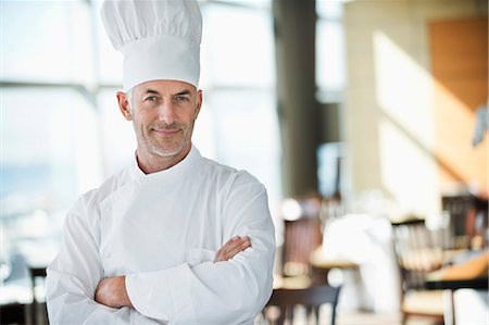 Portrait of a chef smiling with arms crossed in a restaurant Stock Photo - Premium Royalty-Free, Code: 6108-06906704