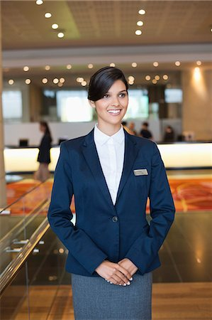 services - Receptionist standing in a hotel lobby and smiling Stock Photo - Premium Royalty-Free, Code: 6108-06906720