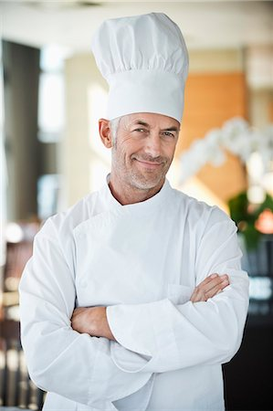 Portrait of a chef smiling with arms crossed Stock Photo - Premium Royalty-Free, Code: 6108-06906721