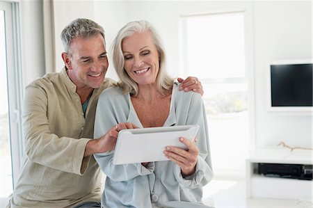 Smiling senior couple using a digital tablet Stock Photo - Premium Royalty-Free, Code: 6108-06906850