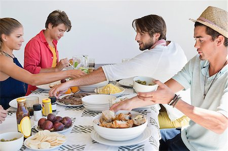 eating - Friends eating lunch at dining table Stock Photo - Premium Royalty-Free, Code: 6108-06906817