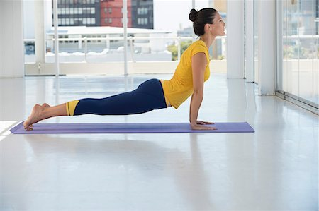 stretching (people exercising) - Woman exercising on exercise mat in a gym Stock Photo - Premium Royalty-Free, Code: 6108-06906943